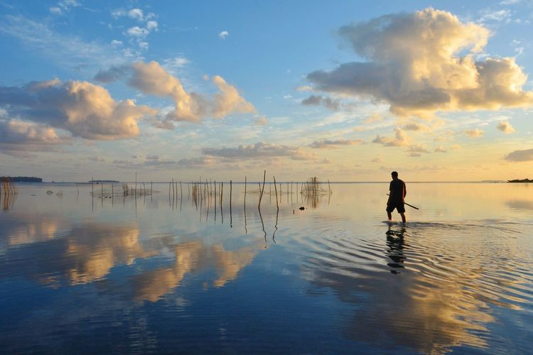 Man Walking In Sea Against Sky During Sunset