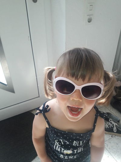 Portrait of girl wearing sunglasses at home