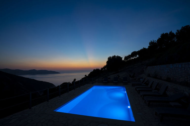 Scenic view of swimming pool against clear sky at sunset