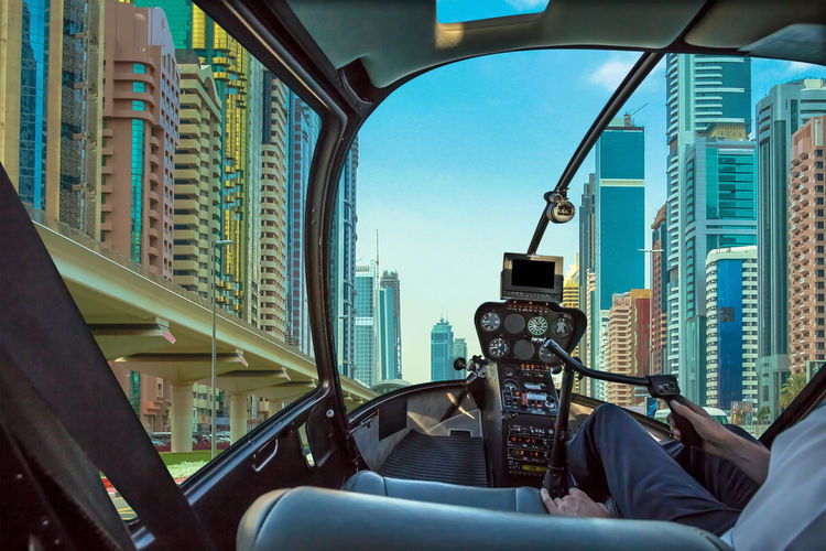 Digital composite image man flying helicopter amidst buildings in city