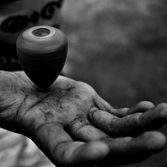 Cropped image of spinning top on hand