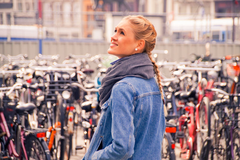 Young woman standing at bicycle parking station outdoors