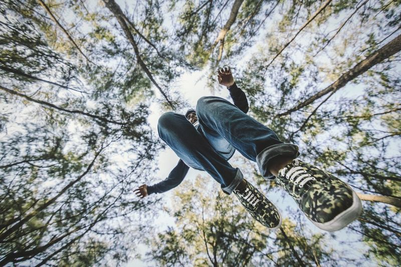 Directly below shot of man jumping against trees