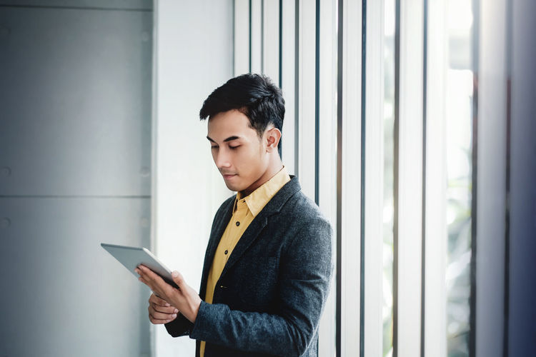 Portrait of Happy Businessman Standing by the Window in Office. Using Digital Tablet and Smiling One Person Wireless Technology Technology Real People Communication Connection Holding Standing Waist Up Digital Tablet Casual Clothing Young Adult Indoors  Lifestyles Clothing Males  Looking Side View Indoors  Asian  Businessman
