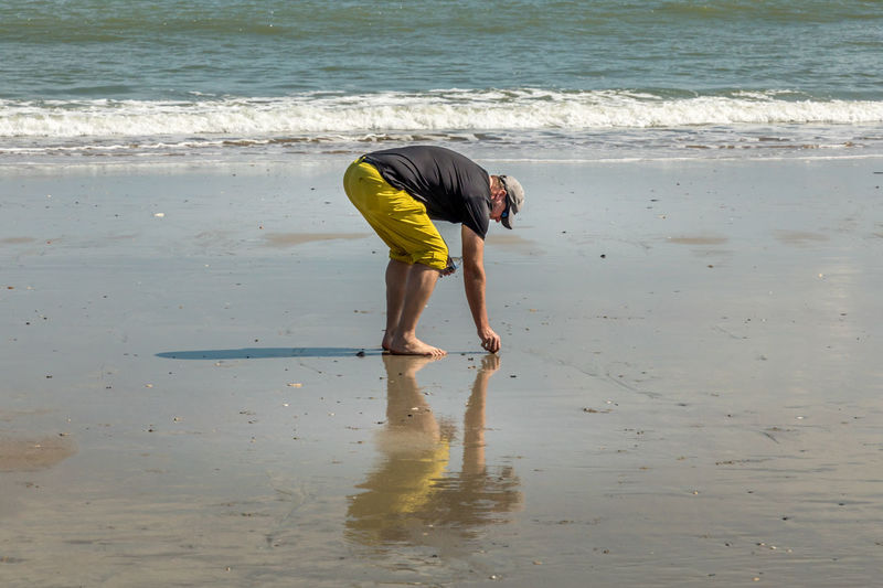Enjoying the beach Man Tourist Vacations South Carolina Springtime Ocean USA Adult Water Beach Land Sea Full Length Bending Real People One Person Leisure Activity Men Beauty In Nature Day Lifestyles Nature Sand Motion Standing Wet Outdoors Bending Over