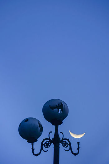 Low angle view of broken street light against clear blue sky