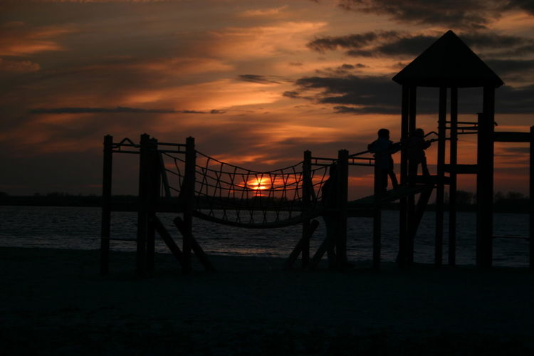 People on jungle gym at beach against sky during sunset