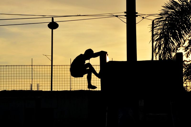 Silhouette boy climbing on wall against sky during sunset