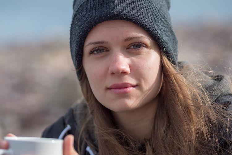 Close-up portrait of woman wearing knit hat