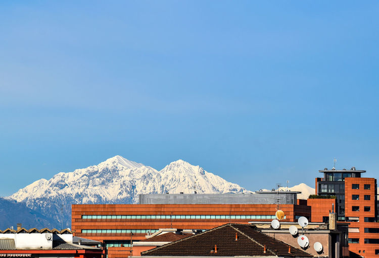 Houses against snowcapped mountains against clear sky