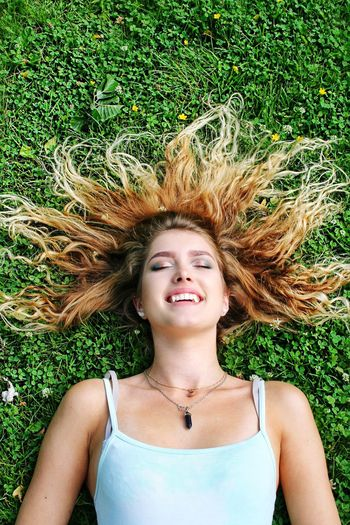 Portrait of a smiling young woman lying down on field