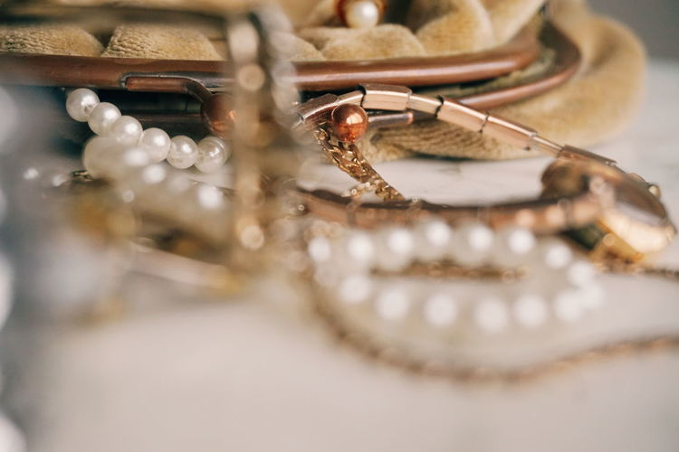 Close-Up Of Jewelry By Purse On Table