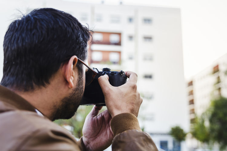 Close-up of man photographing buildings with camera
