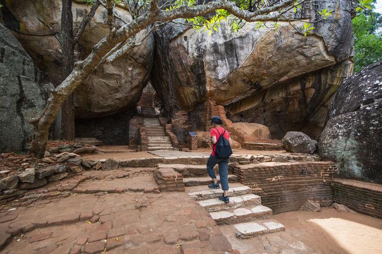 Rear view of woman walking on rock