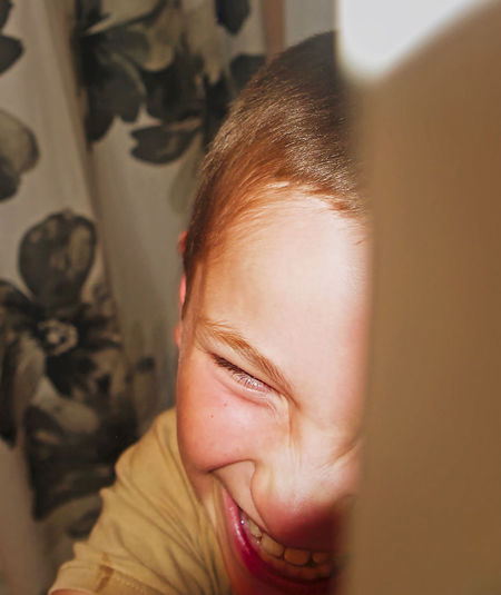 Close-Up Of Cheerful Teenage Boy At Home