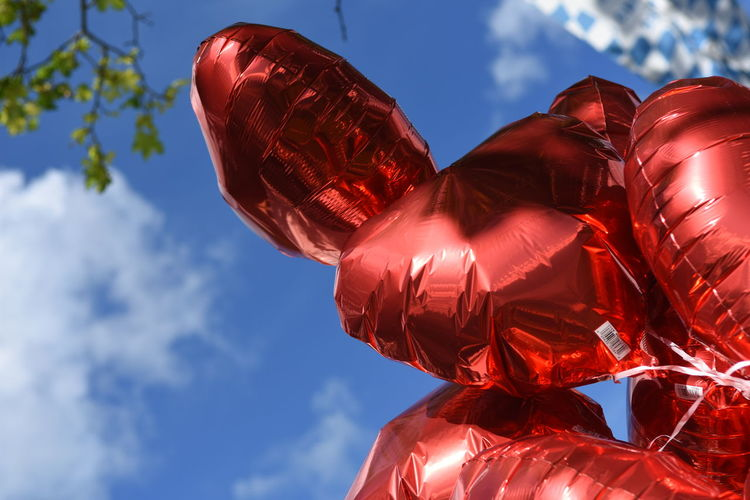 Low angle view of red helium balloons against sky