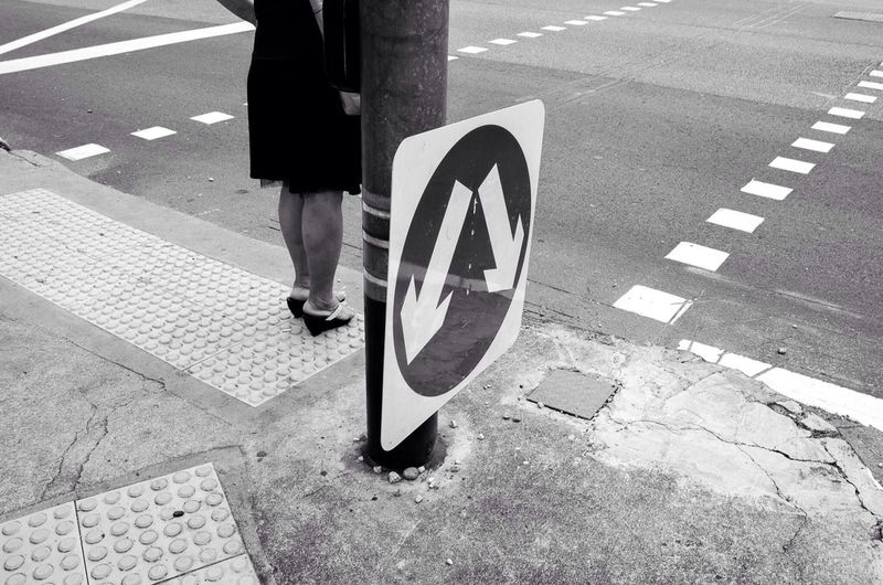 Low Section Of Woman Standing On Sidewalk By Arrow Symbols