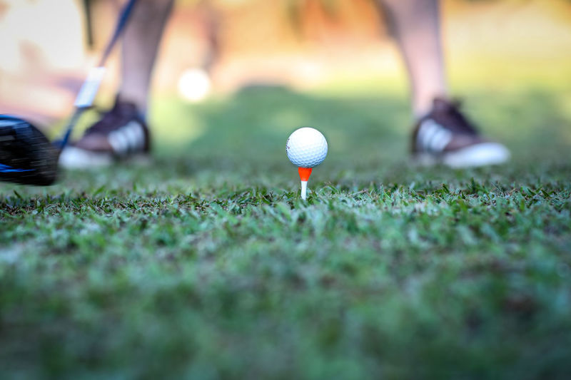 Golf Golf Sport Grass Leisure Activity Golf Ball Selective Focus Low Section Activity Golf Course Ball Green Color Human Leg Weekend Activities Day Green - Golf Course Outdoors Surface Level Golf Club Golfclub Competition Shallow Depth Of Field Tee Golf Tee