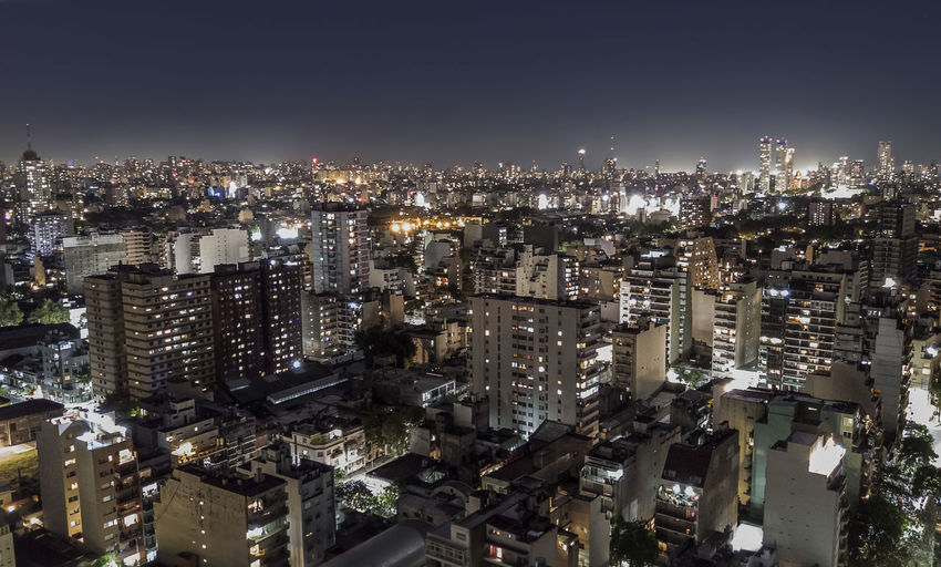 Illuminated cityscape against clear sky at night