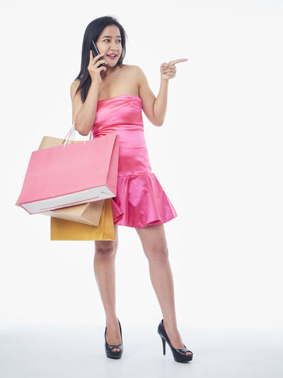Full length of a young woman using phone against white background