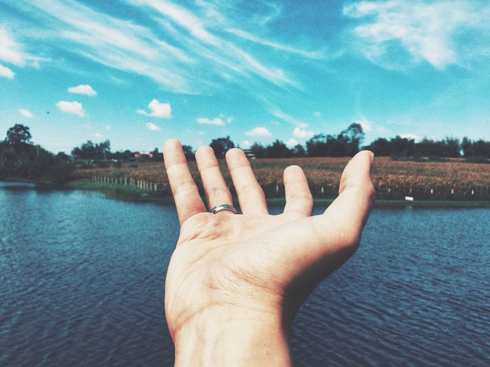 Close-up of hand over lake against sky