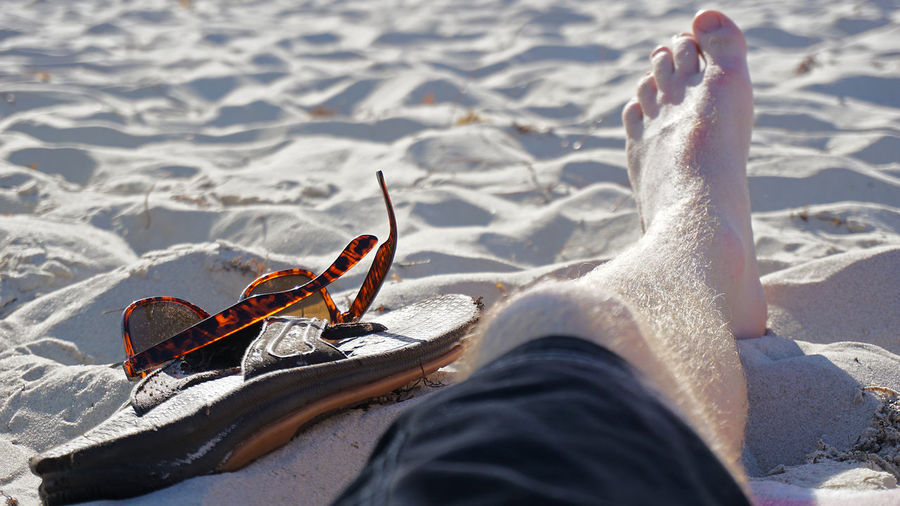 Low Section Of Man By Slippers And Sunglasses On Sand At Beach