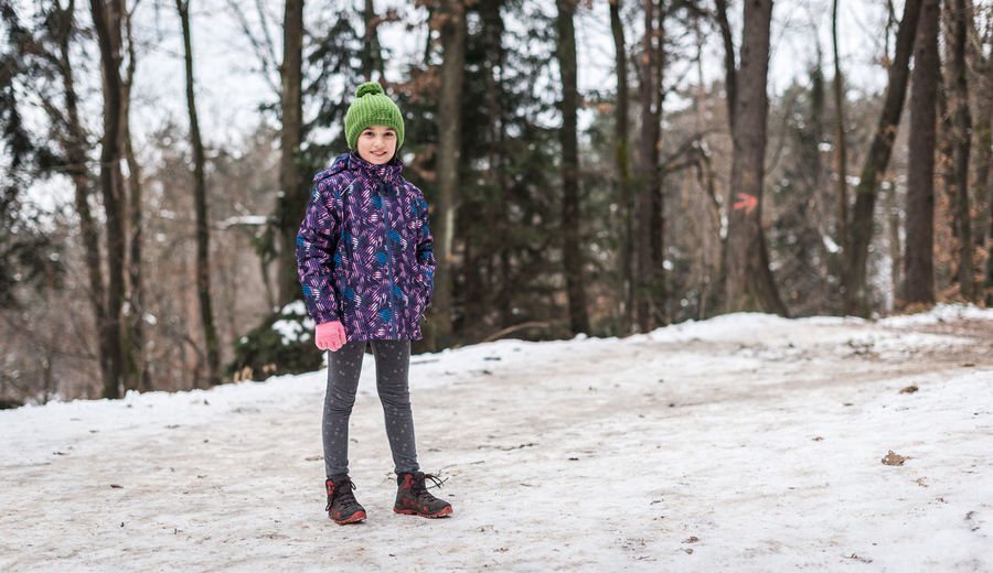 Portrait of boy standing on snow covered land