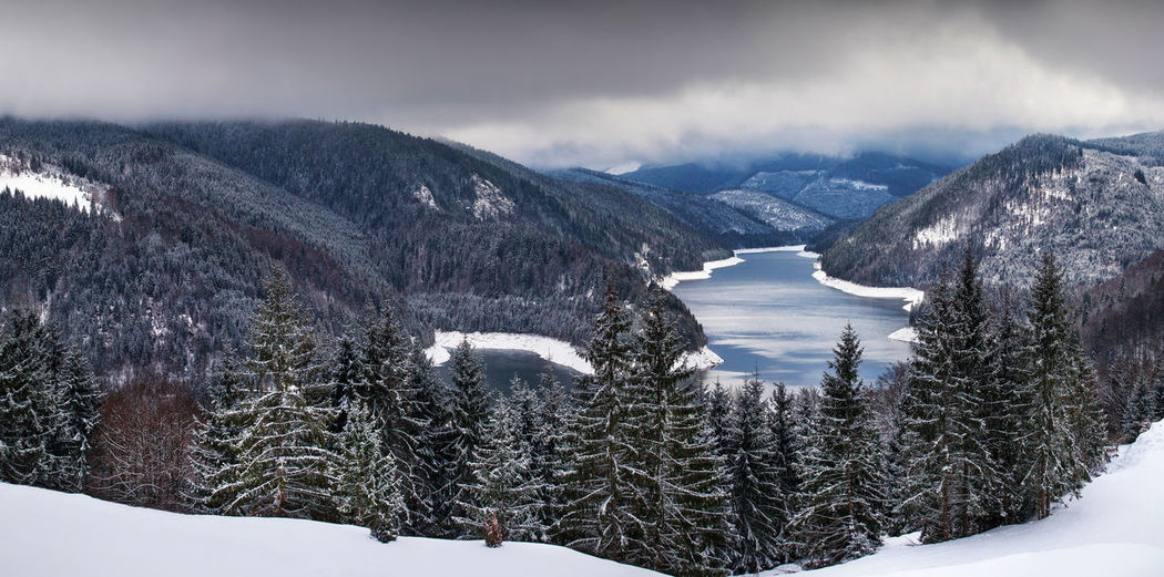 Panoramic view of frozen river amidst mountains during winter