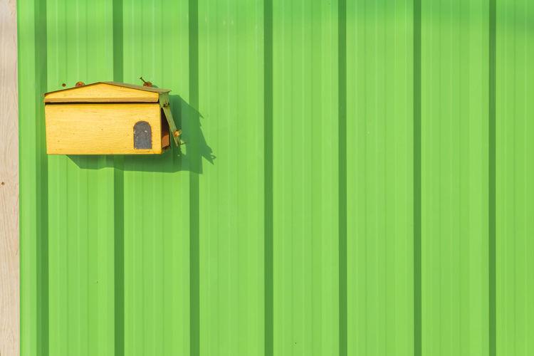 Birdhouse on green corrugated iron
