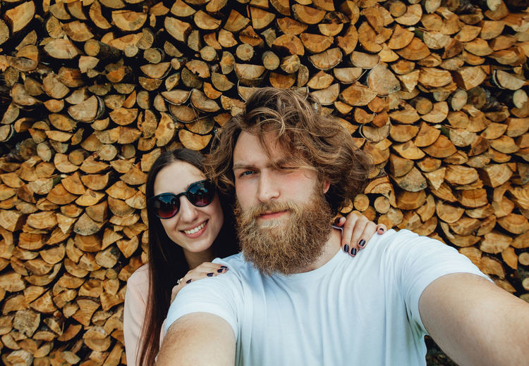 Portrait Of Couple Standing Against Stacked Logs