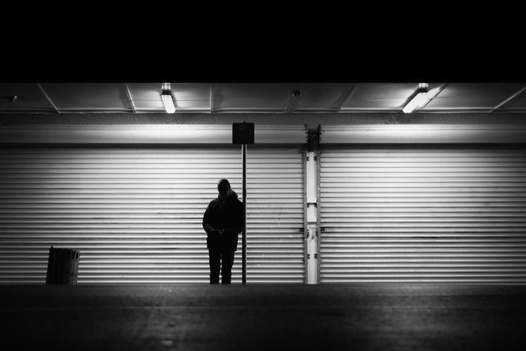Rear view of silhouette man walking in illuminated corridor