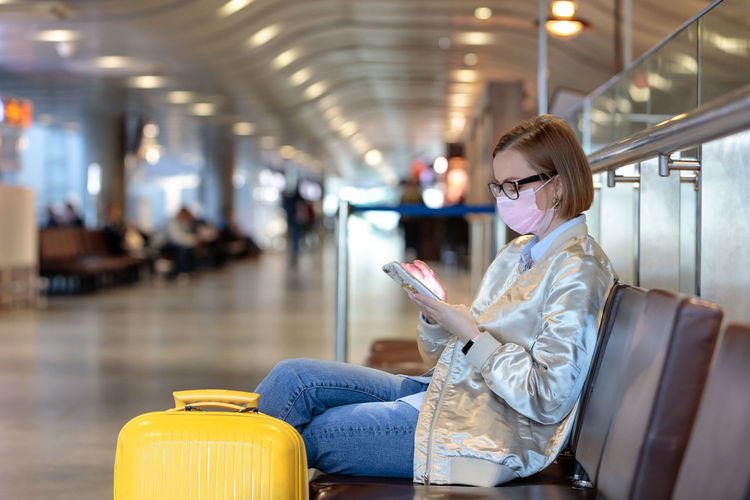Woman using mobile phone while sitting by suitcaase at airport