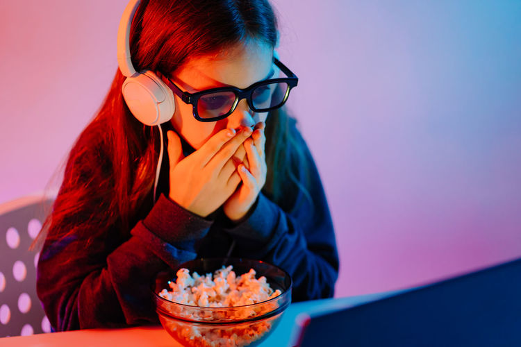 Girl watching movie on laptop at home