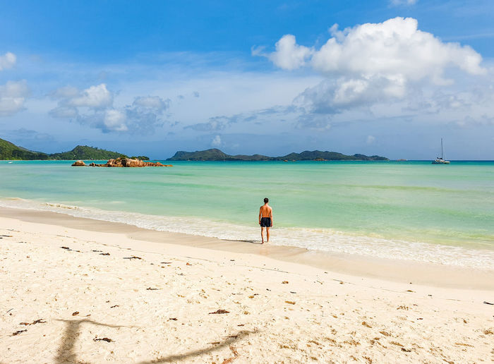 One person at vast sandy tropical beach.