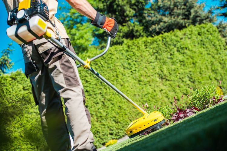 Low section of man cleaning garden with equipment
