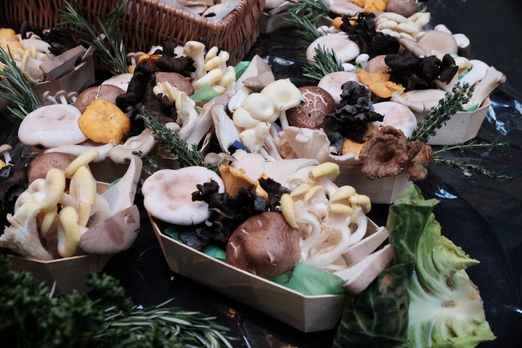 High Angle View Of Edible Mushrooms In Containers On Table
