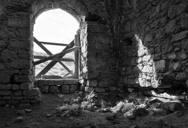 Old ruin building against sky seen through window