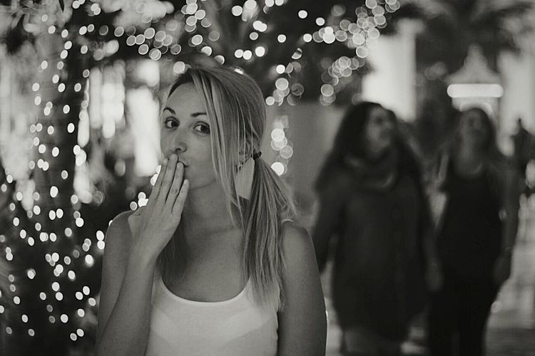 Portrait Of Young Woman Giving Flying Kiss By Illuminated Lights