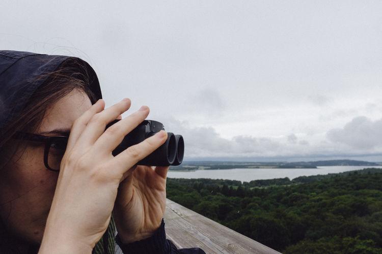 Close-up of woman looking through binoculars against sky