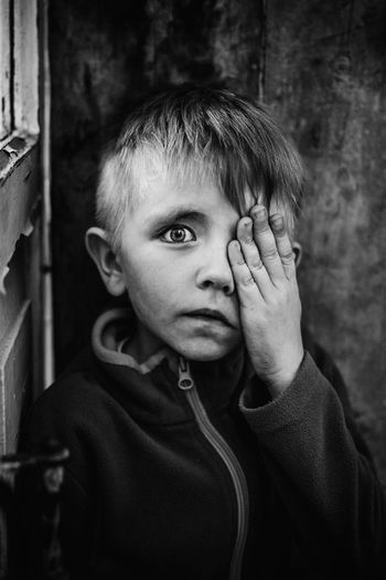 Portrait of boy hiding on eye by hand against wall