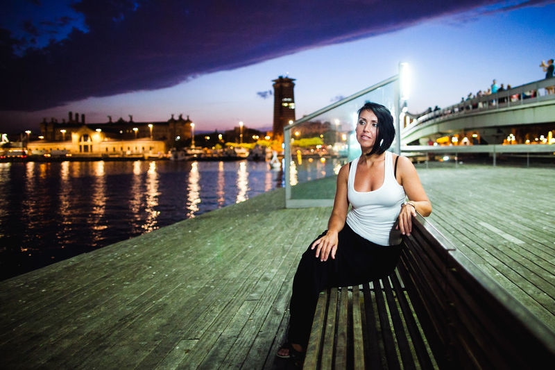 Woman sitting on bench against sky in city at dusk