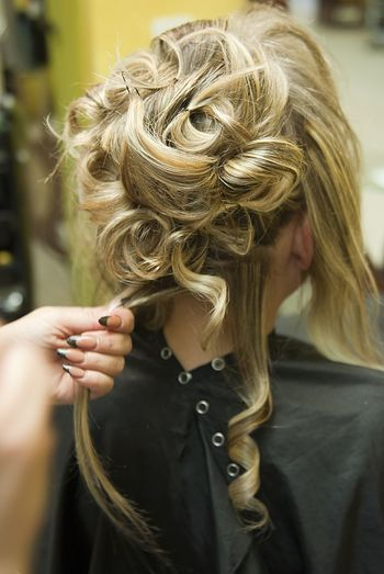 Cropped hand of hairdresser adjusting woman hair