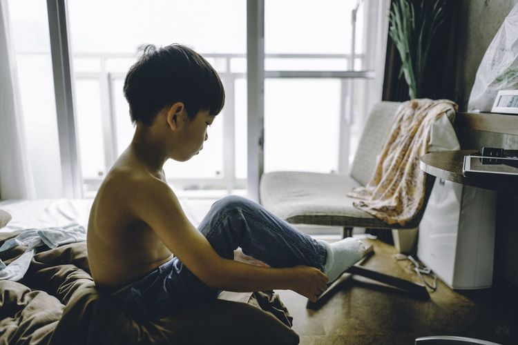 Shirtless Boy Wearing Sock On Bed At Home