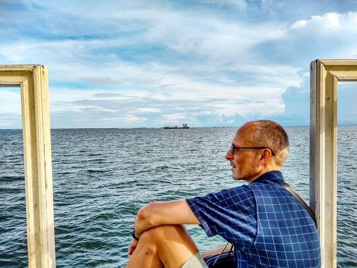 Man looking at sea against sky