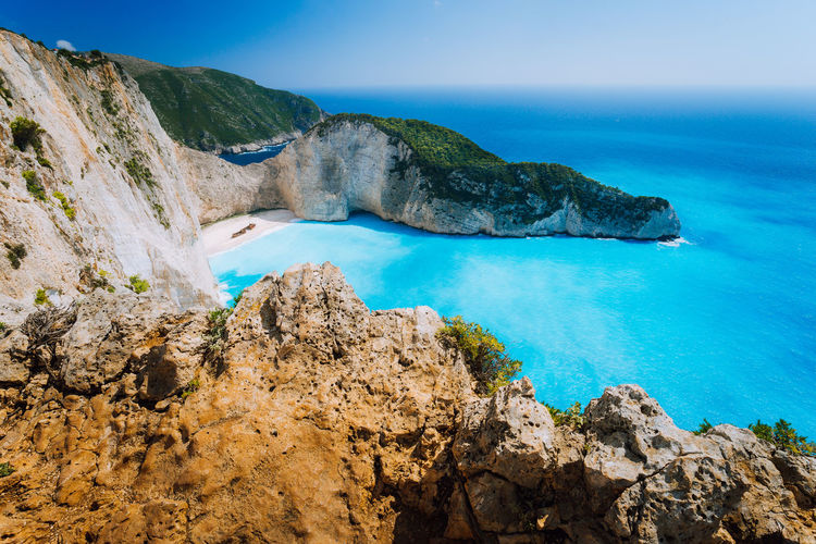 Rock Cliffs in front of Navagio beach Zakynthos. Shipwreck bay with turquoise water and white sand beach. Famous marvel landmark location in Greece Sea Water Beauty In Nature Scenics - Nature Rock Rock - Object Solid Nature Tranquil Scene Tranquility Blue Day Mountain Beach Rock Formation Non-urban Scene Outdoors Turquoise Colored Horizon Over Water Lagoon Bay Navagio Beach Marvel Hidden Places Greece
