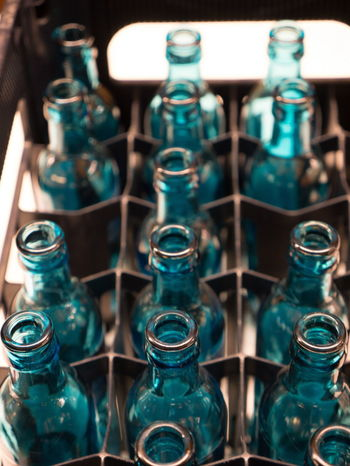 Glass - Material Indoors  Close-up Bottle Still Life Transparent No People Large Group Of Objects Container Glass In A Row Arrangement Selective Focus High Angle View Choice Full Frame Focus On Foreground Empty Rack Blue