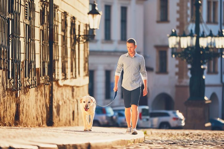 Portrait Of Man With Dog Walking In Front Of Building