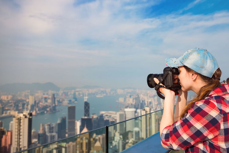 Woman photographing cityscape against sky