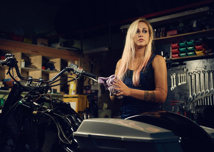 Young Woman Standing By Motorcycle At Workshop