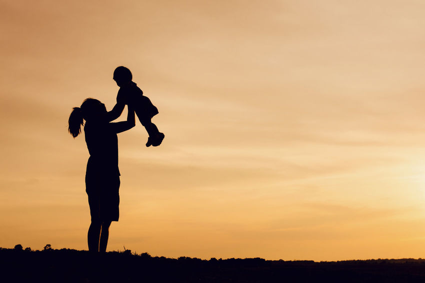 Happiness Kids Lifting Love Mother Mother & Daughter Silhouette Beauty In Nature Child Daughter Lifestyles Love Kids Love Mom Mother Day Orange Color Park Playing Real People Silhouette Sky Standing Sunrise Sunset Sunsets Women